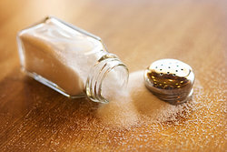 open salt shaker lying on table with salt spilling out