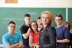 smiling teacher and high school students in classroom