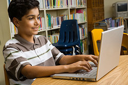 a student typing on his laptop