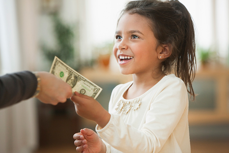 child being handed allowance
