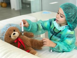 Boy offering medical care to teddy bear