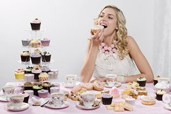 Woman indulging in doughnuts and cupcakes