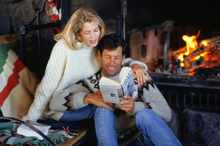 couple reading in front of fireplace