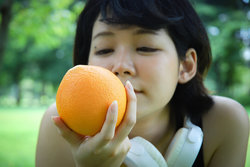 woman looking closely at orange