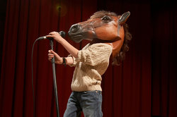 boy wearing horse mask on stage