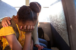 girl consoling crying friend on bus
