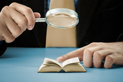 reading small book with magnifying glass
