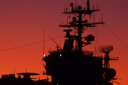 silhouette of naval ship against red sky