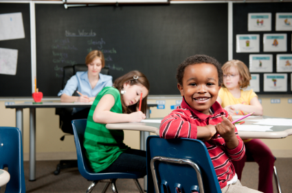 child smiling at camera in 1st grade classroom
