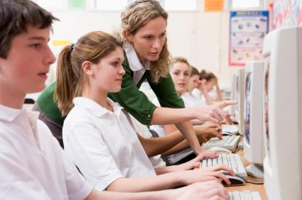 students at computers with teacher