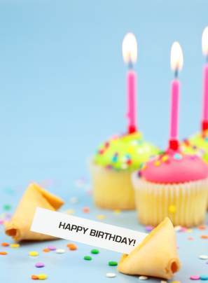 open fortune cookie with happy birthday message and cupcakes with candles