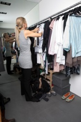 A woman searches her closet for something to wear.