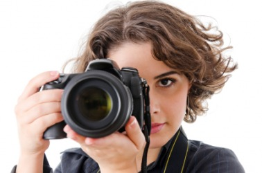 A woman takes a picture with her camera.