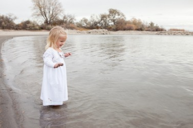A little girl wades in the water.