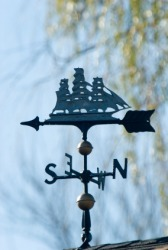 A weather vane in the shape of a ship.