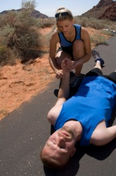 A woman assists an unconscious man.