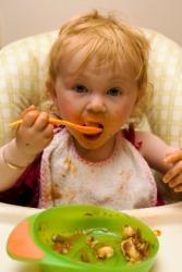 A little girls eats her din-din.