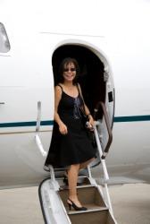 A woman disembarks a plane.