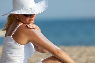 A woman applies an emollient to her skin.