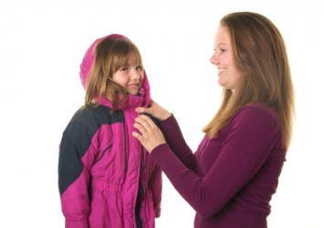 A mother fastens her daughters coat.