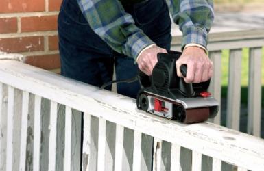 A man fixes the railing of his porch.