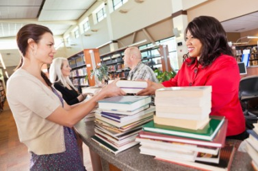 A librarian helps people check out books.