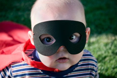 A cute baby wearing a mask.