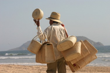 A man peddles baskets on the beach.