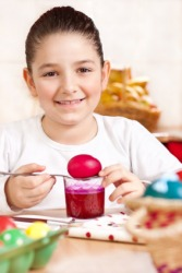 A girl colors an egg using red dye.