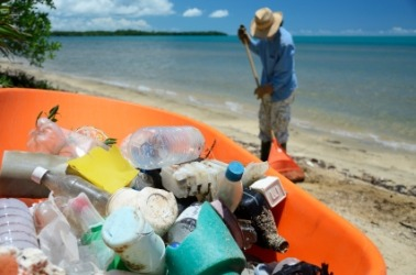 A man collects trash on the beach.