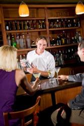A bartender serves drinks.