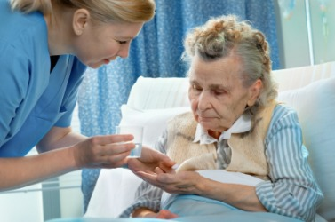 A nurse administers medicine to her patient.