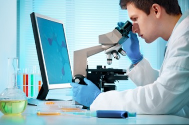 A scientist examines something under a microscope.