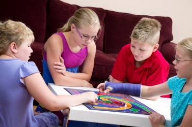 Children interact while playing a board game.