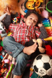 A child lays in a jumble of toys.