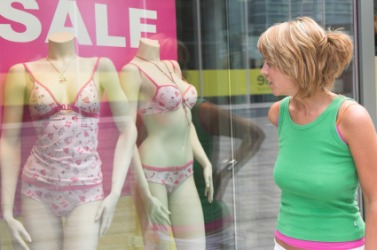 A woman looks at lingerie in a shop window.
