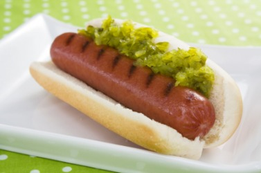 A hot dog covered with relish.