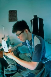 A young man sewing with a sewing machine.