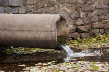 Raw sewage flows from a pipe polluting a river.