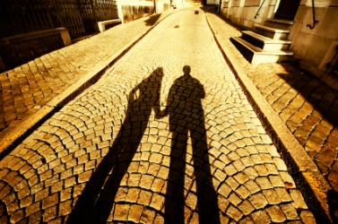 Two long shadows on an old street.