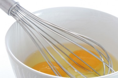 A whisk in a bowl of eggs.