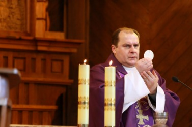 A Catholic priest observes the rite of communion.