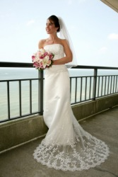 A woman poses in her wedding gown.