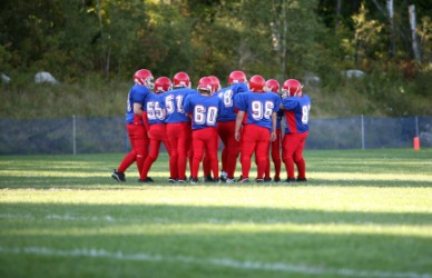 Young football players in a huddle.