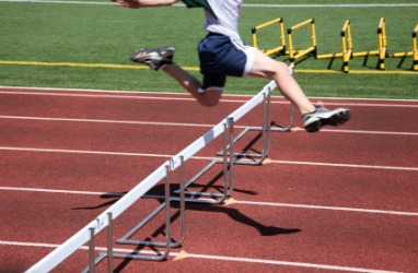 A runner jumps over a hurdle.