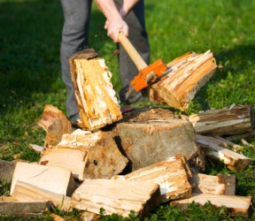 A man hacks at a pile of wood.