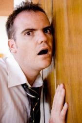 A man trying to listen through a door.