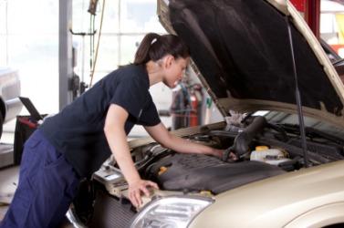 A mechanic checks the engine of a car.