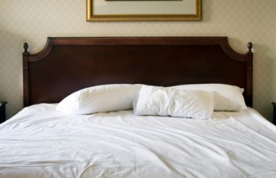 A Bed Covered With White Sheets.