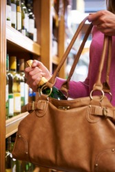 A woman shoplifts a bottle of wine.